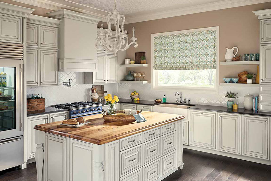 A kitchen with white cabinets and tile backsplash, an island with a wood countertop on hardwood floors.