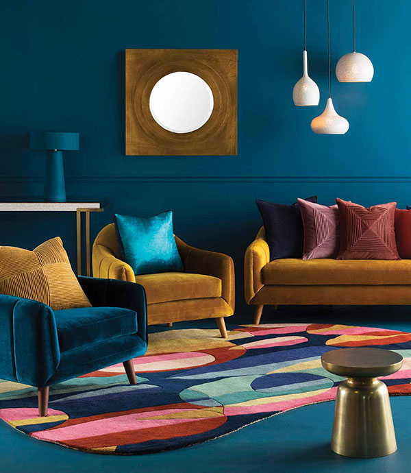 A living room filled with Memphis design themed accessories to a large colorful area rug, blue carpet, and blue and gold chairs.