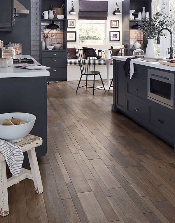 A kitchen with grey cabinets, white countertops and trendy wood floors that are a mix of wide and thin planks.