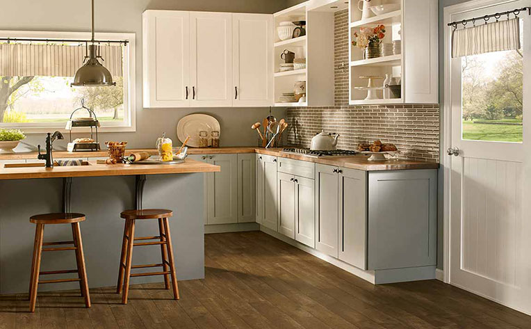 A kitchen with island and bar seating, white overhead cabinets, and grey lower cabinets that accentuate the wood floors.
