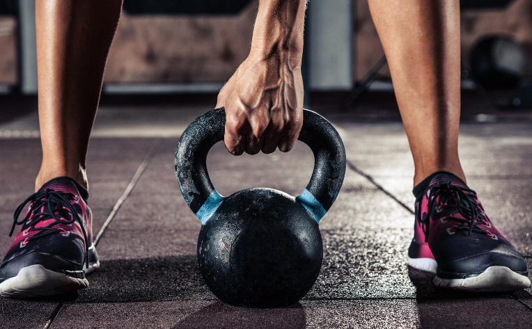 Person grasping kettlebell standing on rubber flooring
