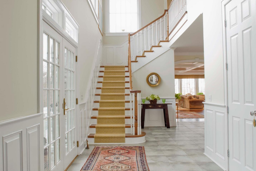 home entrance facing inside home with carpet lined staircase